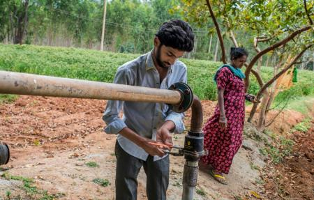 Chidan and Field assistant opens bore well pipe to collect the ground water measurement from the farm of Subbanna.