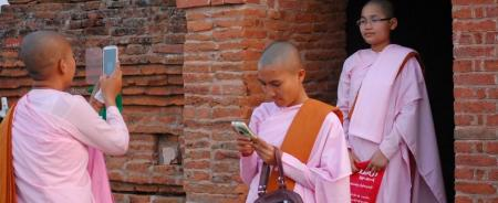 Buddhist nuns taking photos of each other in Myanmar.