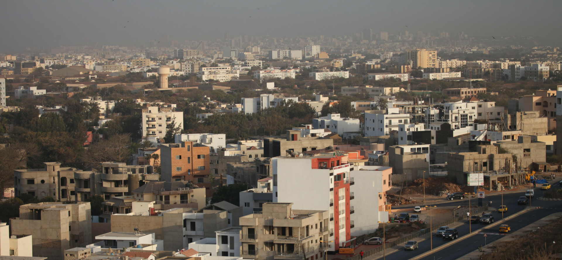 Buildings in Senegal with smog overhead.