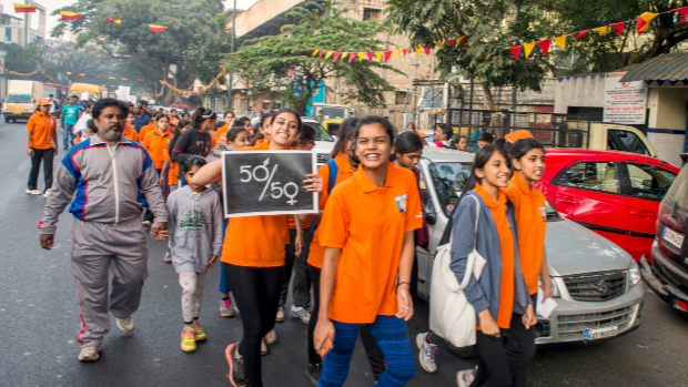 Young girls wearing orange t-shirts march in Bengaluru, India, to protest gender-based violence.