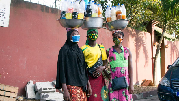 Three young women wearing masks sell medicine on the street during the COVID-19 crisis in Abidjan, Côte d'Ivoire.