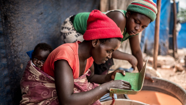Two women, one working with a baby on her back, pan samples of sand for gold at a mining site in central Uganda.