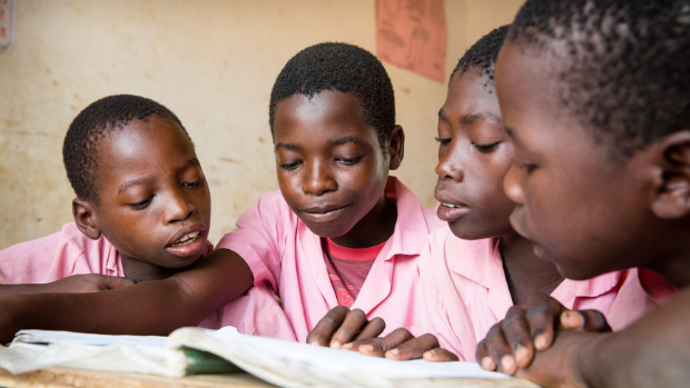 Primary school students consult a book in class in Nyeri County, Kenya.