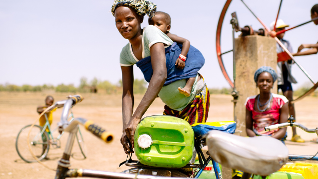 A young woman with her baby on her back fetches water by bicycle.