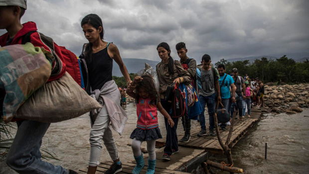 Venezuelan people cross the border to get to Colombia.