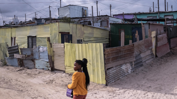 A girl walks past shacks in the township of Khayelitsha, Cape Town, South Africa.