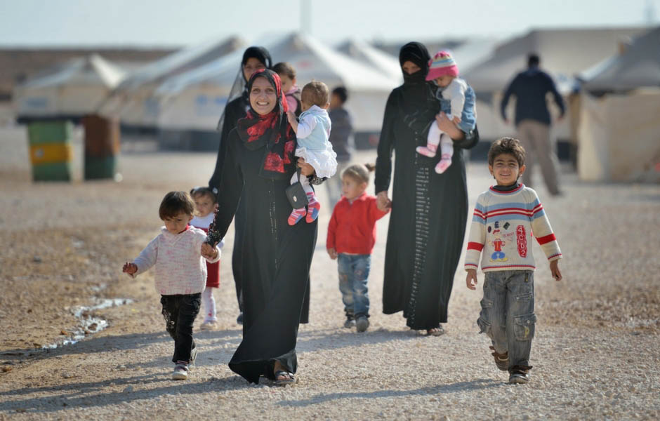 A large family walking in a refugee camp.