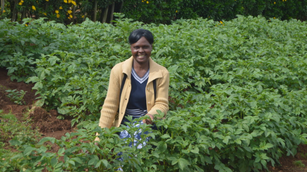 A woman stands among her crops.