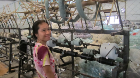 A woman migrant worker from Myanmar operates a textile mill in Thailand.