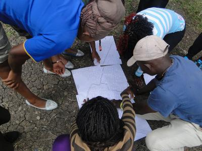 Researchers with the Akiba Mashinani Trust examine a map of Nairobi's Mukuru slum