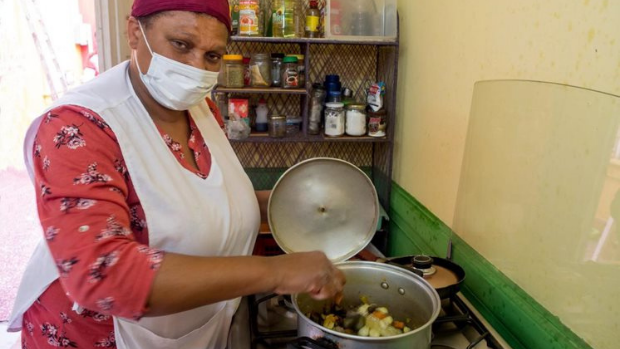 A woman cooks over a stove wearing a mask.