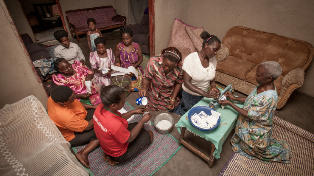 Women from the Busunju cooperative in Uganda unpack a box of milk they obtained.