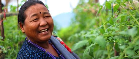 A Nepalese woman demonstrates how her farm has improved since using SAK products.