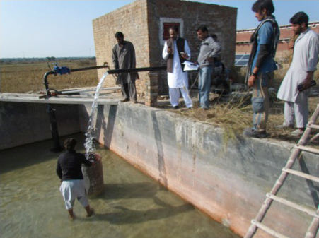 Technicians and farmers watch a solar-powered pump in Pakistan