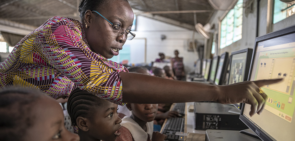 A teacher helping a student with a learning software on a computer in Mombasa, Kenya