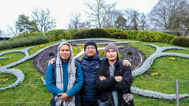 Three young researchers from Myanmar stand in front of flowerbeds in Geneva.