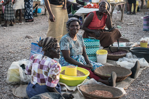 Women sell beans between other stands selling clothing,fruit and vegetables at Rodi Market.