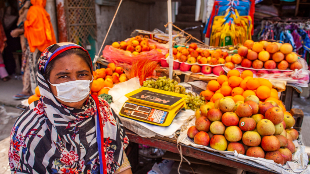 Joba Akter works as a fruit vendor in Dhaka, Bangladesh. She is wearing a mask to avoid the spread of COVID-19.