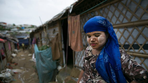 A Rohingya woman refugee, and a Balukhali settlement leader, stands among temporary shelters in this camp in Bangladesh.