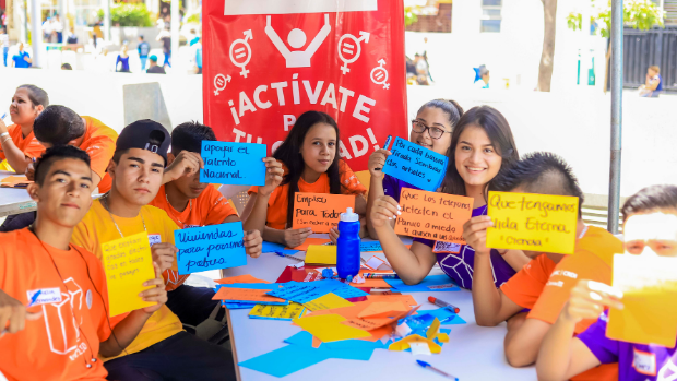 Youth attending a workshop in El Salvador hold up cards expressing what they would like to see in the future.