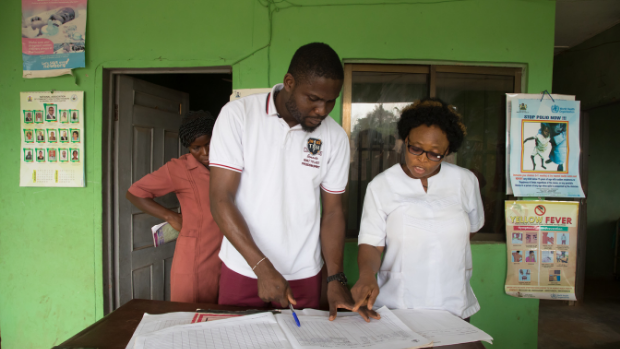 A male and a female health worker review paper records in a clinic in Edo State, Nigeria.