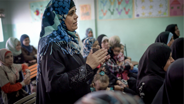 A woman stands in a room full of women during a meeting in Hitteen camp for refugees, Jordan.