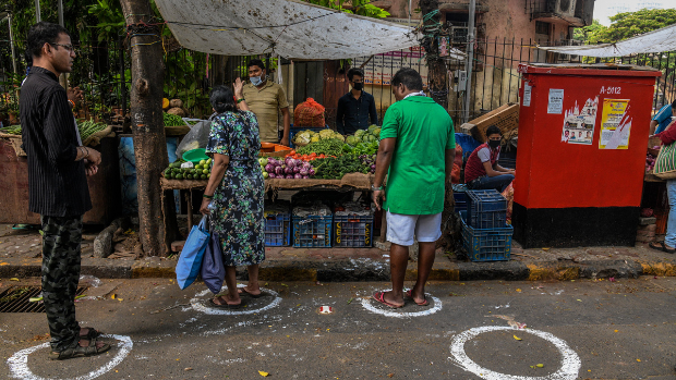 Circles painted on the ground beside stalls selling food to ensure people shopping adhere to social distancing rules during the coronavirus lockdown in Mumbai, Maharashtra, India.