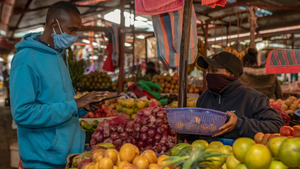 A customer in a mask purchasing fruits from a masked vendor at a local market.