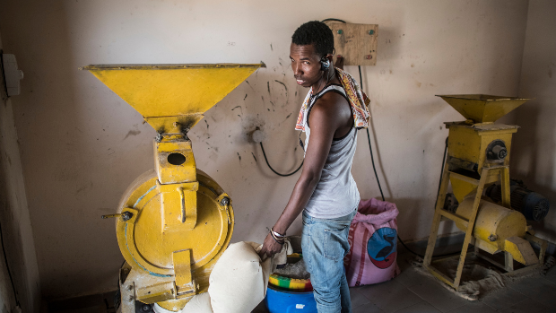 A man operating a mill and grinding equipment in Senegal