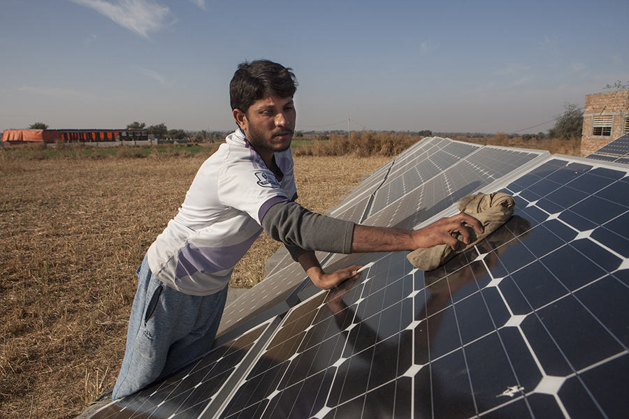 Asif Jehengir cleans A Solar powered water pumping system allows Farmers to irrigate their fields in Talagang, Pakistan