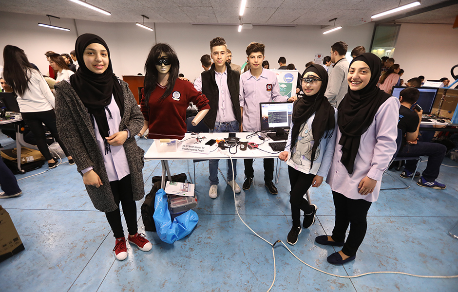 A group of Syrian refugee students in a classroom using electronics
