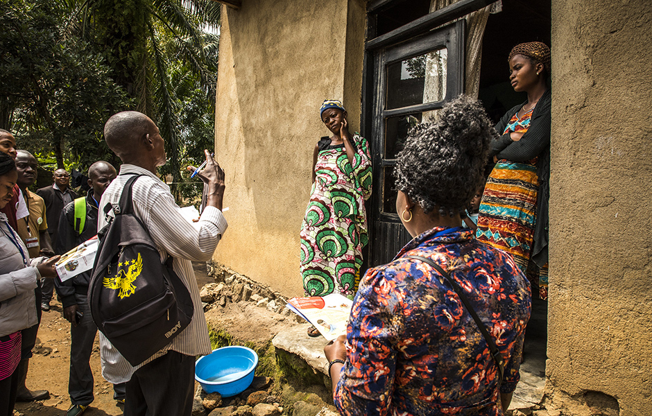 A group of researchers talking to two women in front of their house