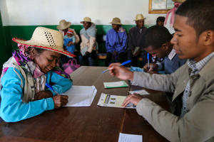 An older woman signing papers