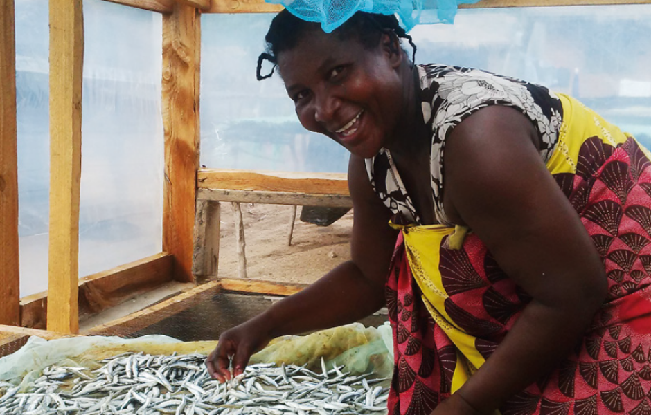 Esnart Mhone drying fish in a solar tent dryer at Msaka