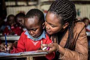 A teacher helping a student in a class room in Nairobi, Kenya