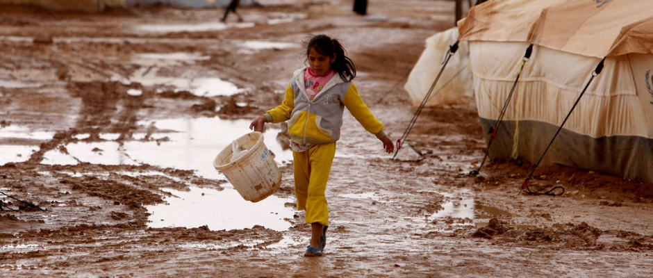 A Syrian girl walks in the mud between tents at Zaatari refugee camp in Jordan.