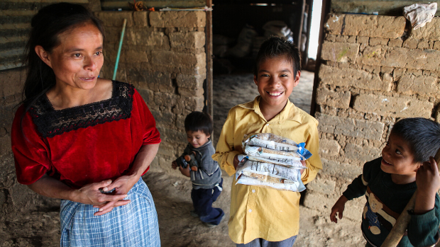 A Guatemalan woman and her children stand inside a house. The eldest holds packages of food.