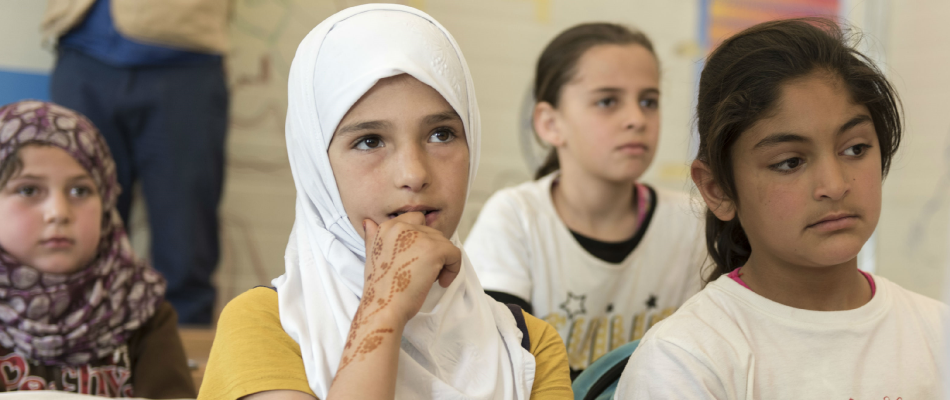 Children listen to their teacher at the Zaatari Refugee Camp, located near Mafraq, Jordan.