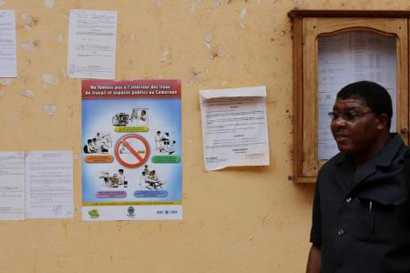 An African man standing in front of a no smoking poster