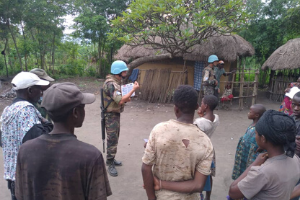 Two Moroccan peacekeepers speak to people in the village of Kiwanja in the Democratic Republic of Congo.