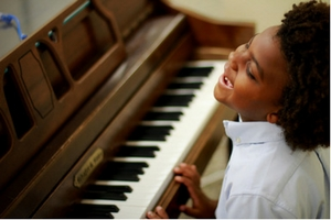 A young boy playing the piano