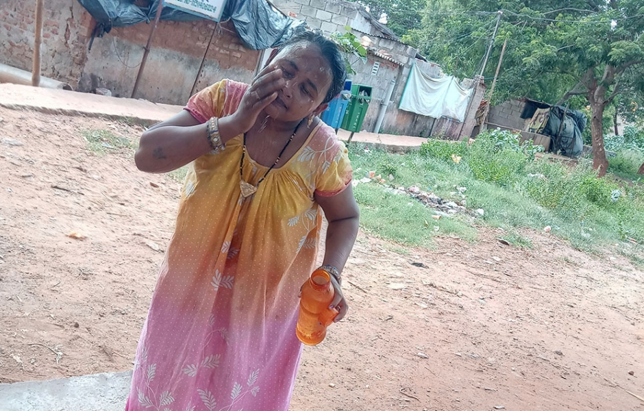 A woman in Bhubaneswar's Mahavir Nagar slum wipes cold water over her face in an effort to cool off.