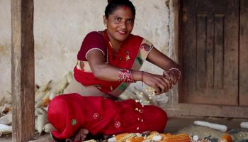 A woman in Nepal uses a corn sheller to save time and reduce the physical toll of her work.