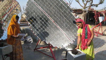 Two women from India are building round solar panels.