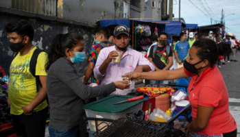 Street vendor outside police station in Escuintla, Guatemala. Marta Gomez's favourite spot used to be the bus station, but restrictions forced it to shut. People are buying coffee and sandwiches and wearing masks.