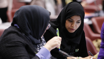 Two women participants converse during an Inter-Parliamentary Union meeting.