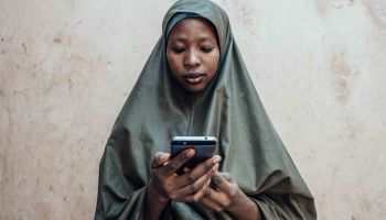 A Nigerian woman holds a mobile phone.