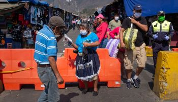 Masked shoppers exit an open-air market in Antigua, Guatemala, during the COVID-19 pandemic.