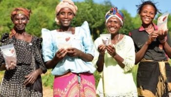 Four women smiling, holding bags of pre-cooked beans.