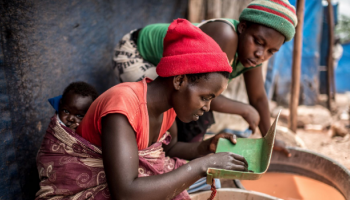 Two women, one working with a baby on her back, pan samples of sand for gold at a mining site in central Uganda